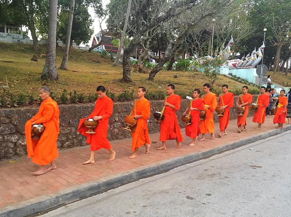 Монахи идут на церемонию раздачи подаяния